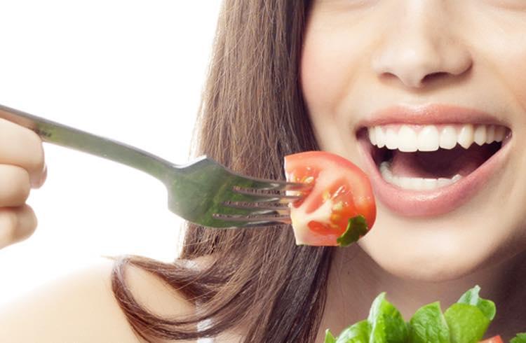 サラダを食べる綺麗な肌の女性