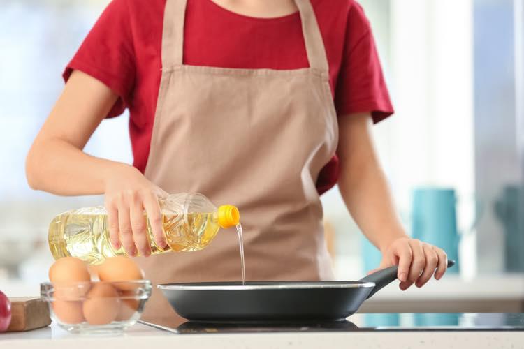 油を使って調理をする女性
