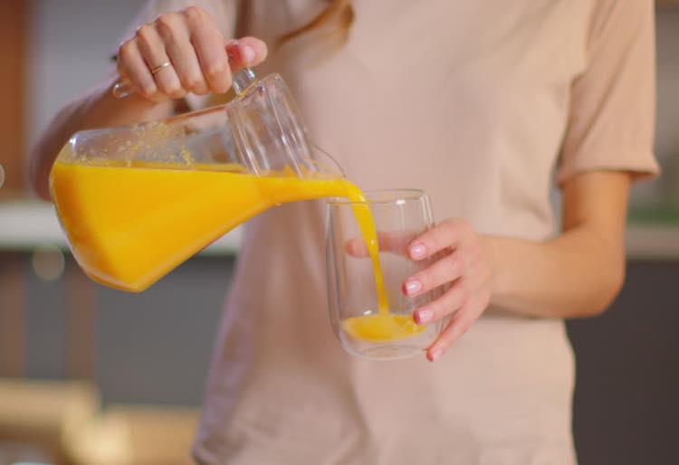 ジュースをグラスに注ぐ女性