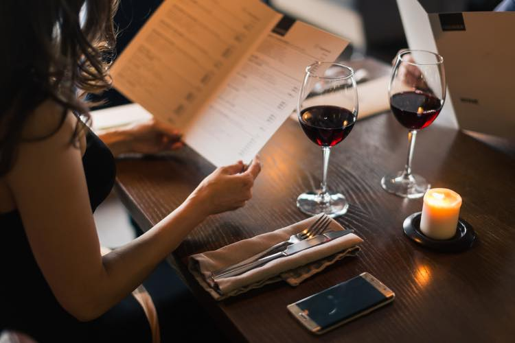 レストランでメニューを選ぶ女性
